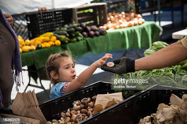 A girl pays for her mother's groceries using Electronic Benefits Transfer tokens more commonly known as Food Stamps at the GrowNYC Greenmarket in...