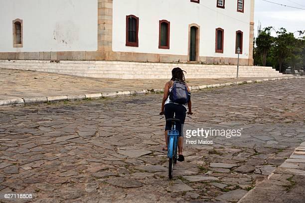 Girl pedaling bicycle in Lençóis street