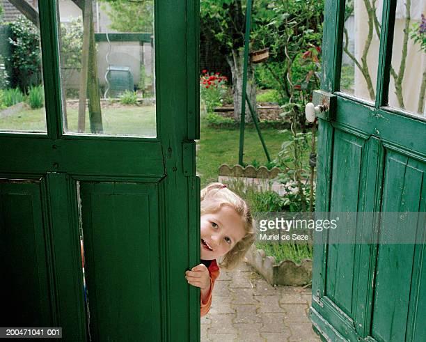 Girl (2-4) peeking around garden door, smiling, portrait