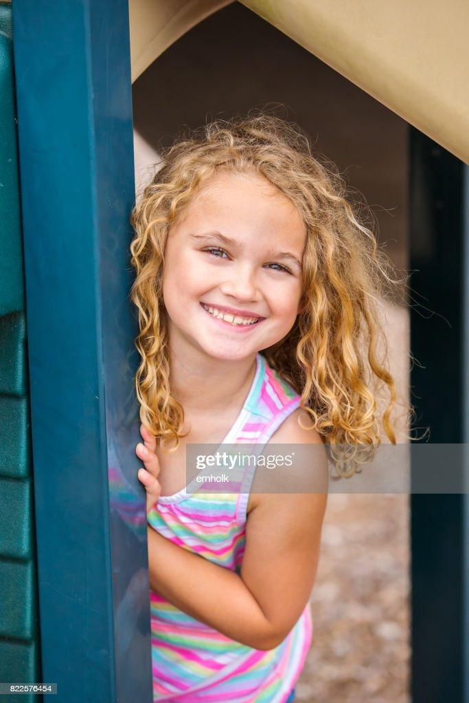 Girl Peeking Around Side of Playhouse at Outdoor Playground : Stock Photo