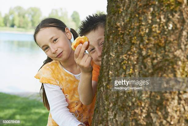 Girl peeking from behind a tree with her brother showing half eaten apple, Bavaria, Germany