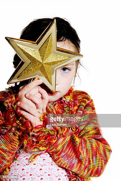 girl peeking from behind christmas star ornament - estrelas de natal imagens e fotografias de stock