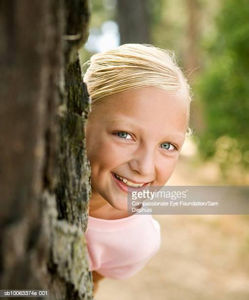 Girl (10-11 years) peeking from behind tree trunk, portrait