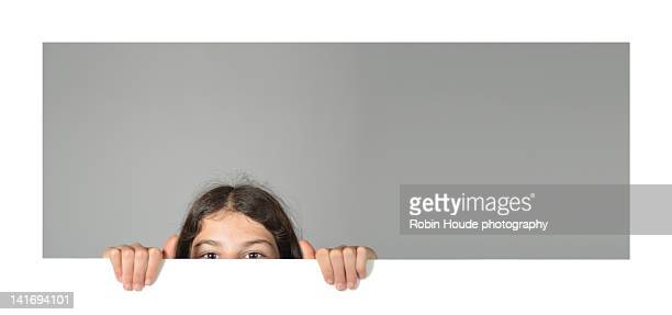 Girl peeking from wall