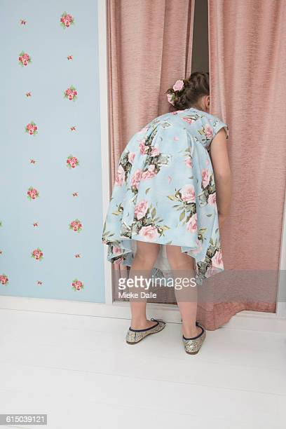 girl peeking out from behind curtain, rear view