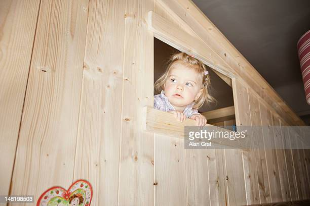 Girl peeking out window of playhouse