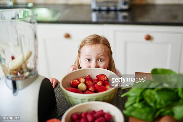 Girl peeking over bowls of strawberries of kitchen counter