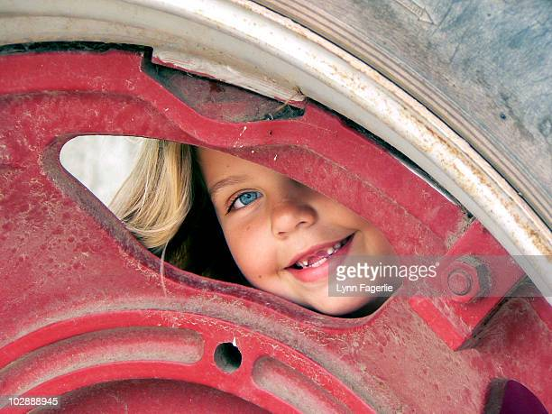 girl peeking through a tractor tire - lynn pleasant stock pictures, royalty-free photos & images