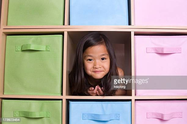 girl peeking through cubed shelving unit - storage compartment stock pictures, royalty-free photos & images