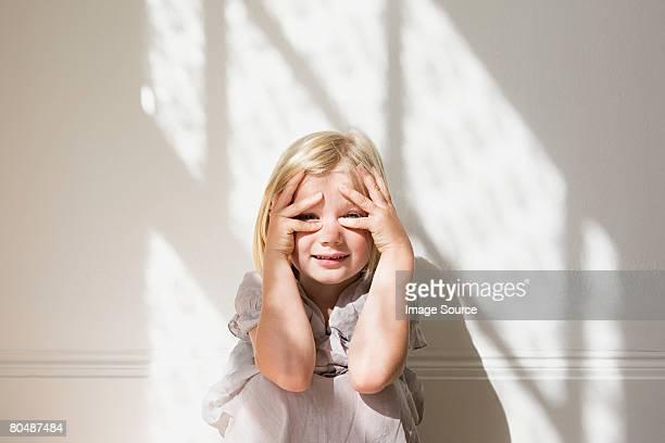 Girl peeking through her fingers