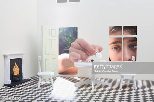 Girl (10-11) peeking through window of dolls house, close-up