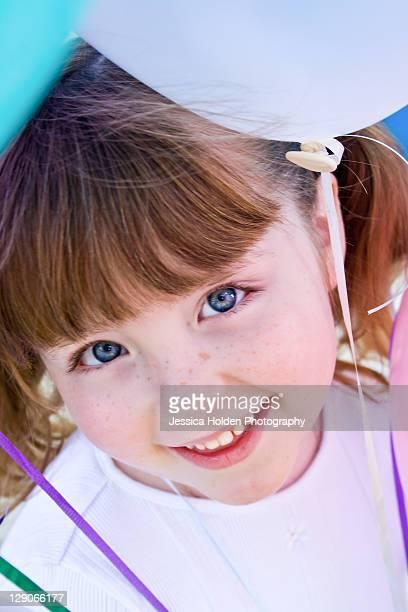 Girl peeking under balloons