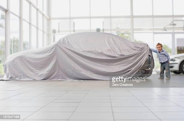 Girl peeking under cloth on car