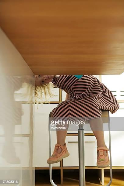 Girl (2-4) peeking under table, sitting in kitchen