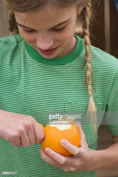 Girl peeling an orange