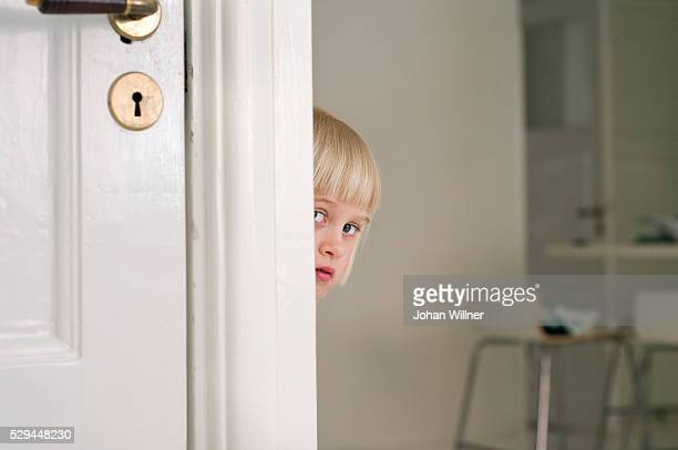 a girl peeping out from behind a corner sweden. - verlegen stockfoto's en -beelden