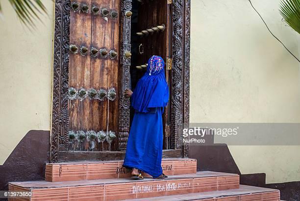 A girl peeps inside a house on a street of the Stone Town in Zanzibar City Zanzibar Tanzania on 11 October 2016