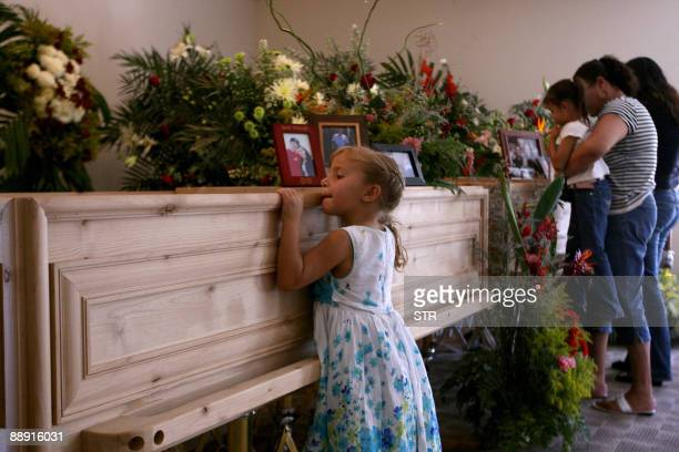 A girl peeps inside the coffin of Mormon church leader Benjamin LeBaron in the LeBaron community in Chihuahua State Mexico on July 8 2009 Lebaron was...