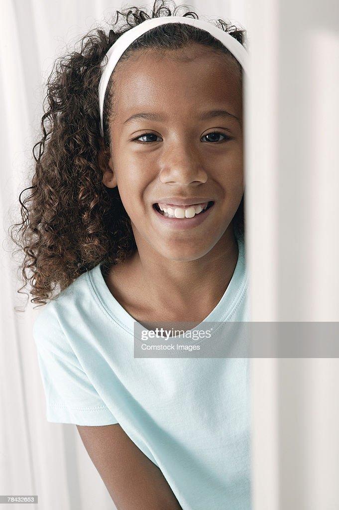 Girl peering from behind computer monitor : Foto de stock