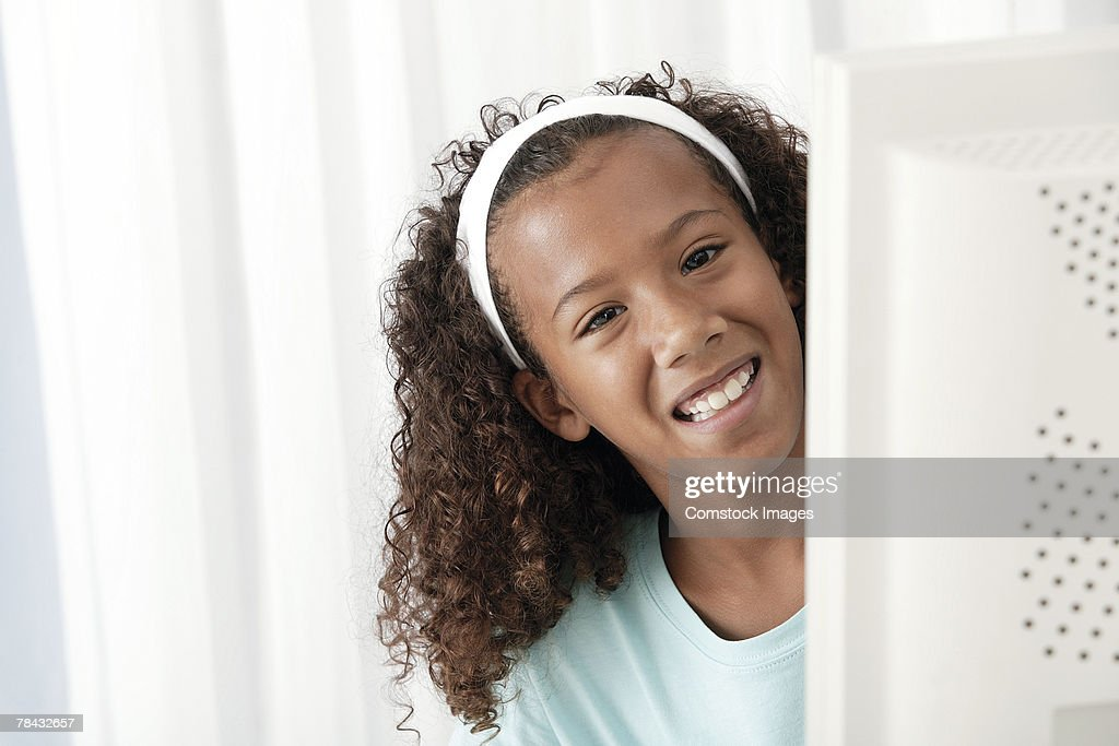 Girl peering from behind computer screen : Stock Photo