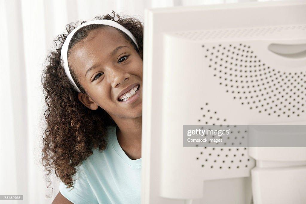 Girl peering from behind computer screen : Stockfoto