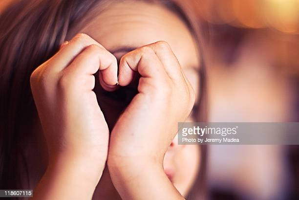 Girl peering hand made heart shape