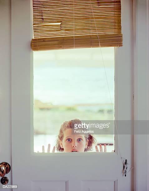 Girl (5-7) peering through window in door, portrait