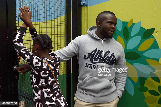 A girl peers through a locked gate at a Kids Company premises on August 5 2015 in Camberwell London England Kids Company a charity for vulnerable...