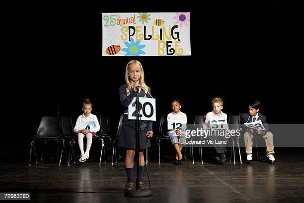 Girl (6-7) performing at spelling bee event