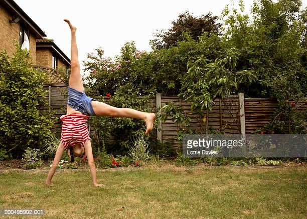 Girl (11-13) performing cartwheel in backyard