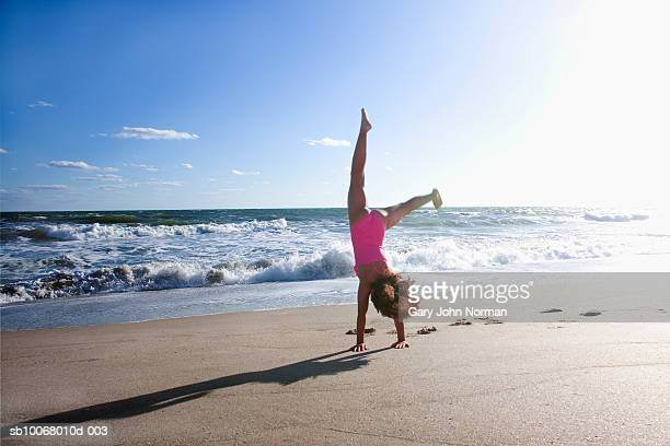 girl (6-7) performing cartwheel on beach - gulf coast states stock pictures, royalty-free photos & images