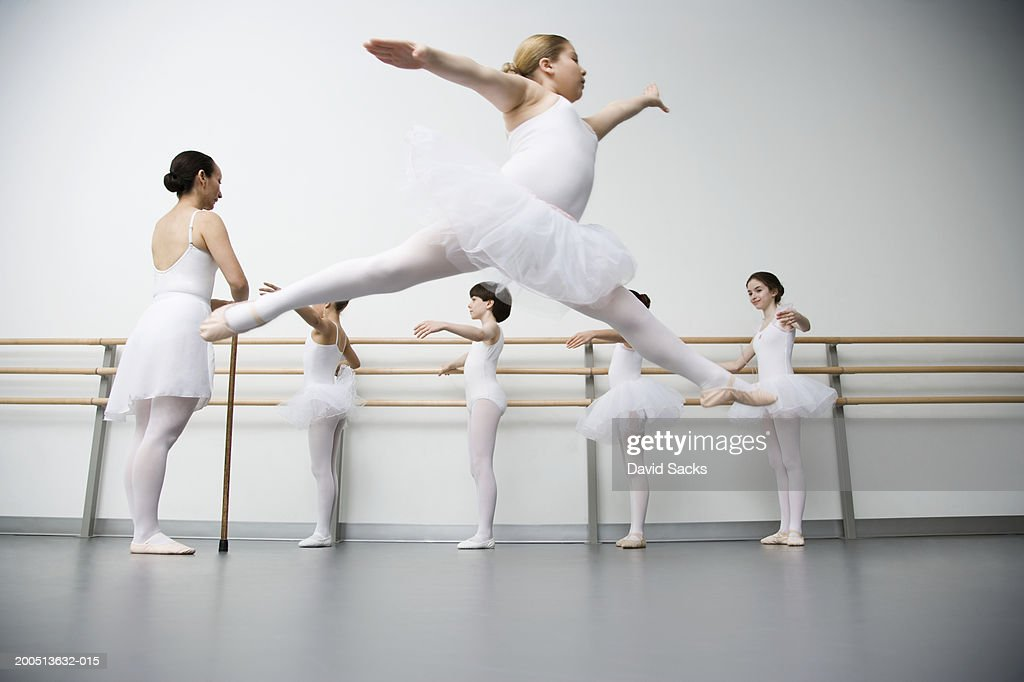 Girl (8-10) performing grande jete in ballet class : Stock Photo