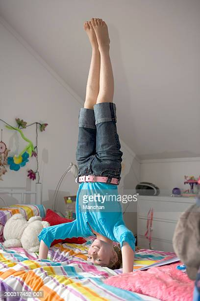 Girl (8-10) performing headstand on bed, smiling, portrait