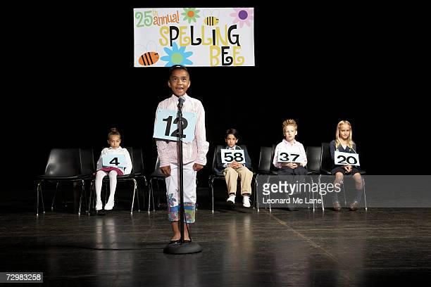 Girl (8-9) performing on stage at spelling bee event