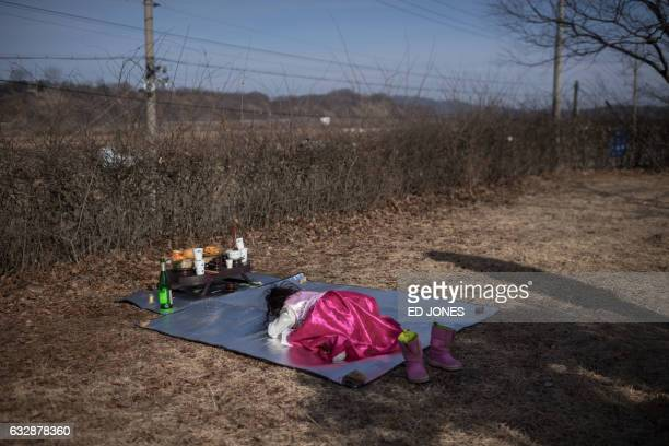 A girl performs a ritual in which prayers are offered for relatives and ancestors in the North before a fence near the Demilitarized Zone separating...