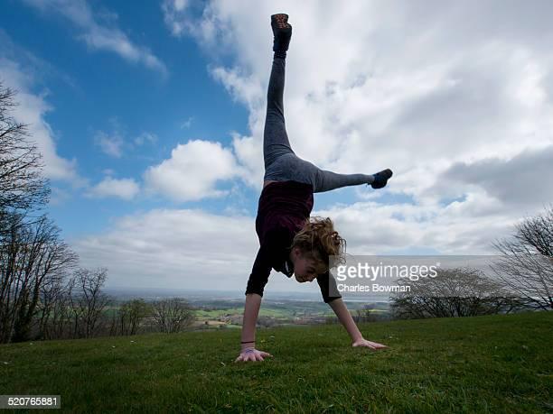 Girl performs cartwheel in Devon landscape