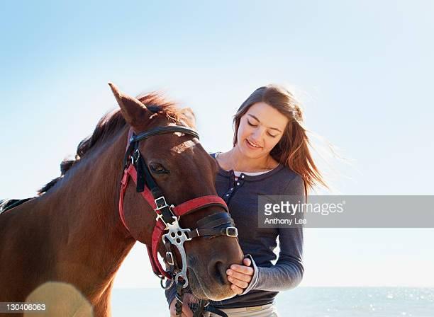 girl petting horse on beach - girl blowing horse - fotografias e filmes do acervo