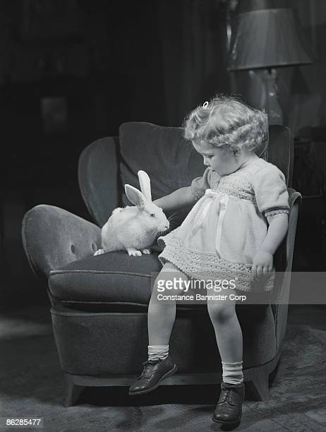 Girl petting white rabbit in armchair