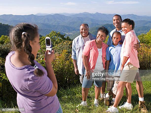 girl (10-11) photographing family with mobile phone - asheville stock pictures, royalty-free photos & images