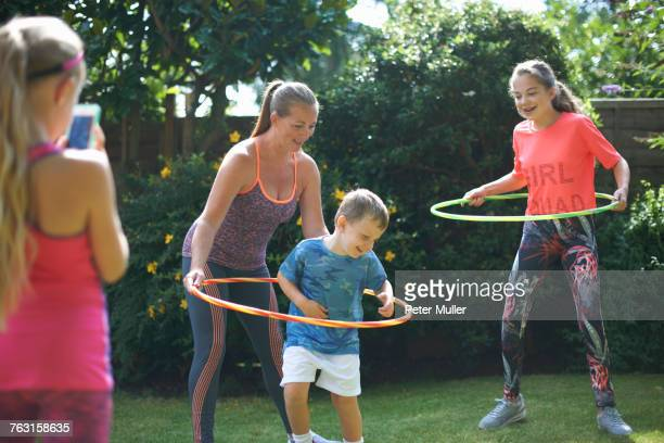 Girl photographing mother and siblings hoola hooping in garden