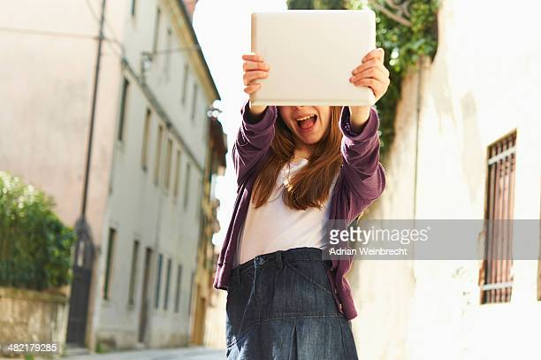 Girl photographing with digital tablet on street, Province of Venice, Italy
