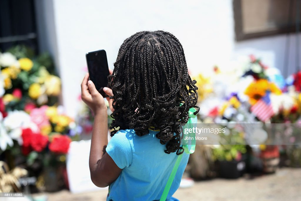 A girl photographs in front of the Emanuel AME Church on the one-month anniversary of the mass shooting on July 17, 2015 in Charleston, South Carolina. Visitors from around the nation continue to pay their respects at a makeshift shrine at the church, in a show of faith and solidarity with 'Mother Emanuel', as the church is known in Charleston. Nine people were allegedly murdered on June 17 by 21-year-old white supremacist Dylann Roof, who was captured by police in North Carolina the following day. He is scheduled to go to trial July 11, 2016.