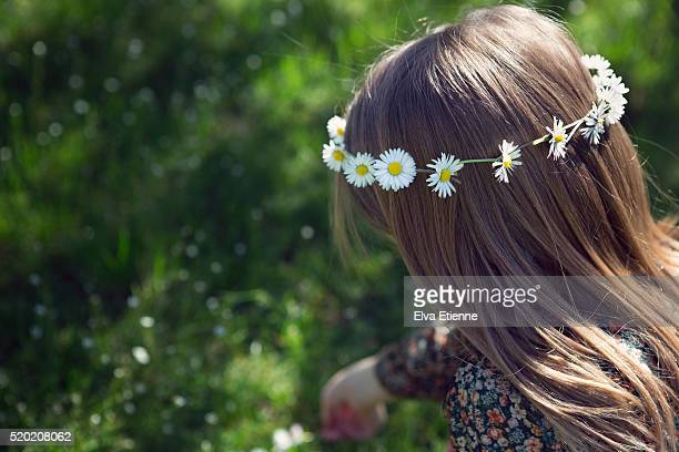 Girl picking daisies and wearing daisy chain