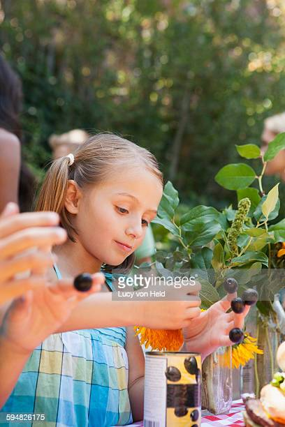 Girl picking flowers and berries in backyard