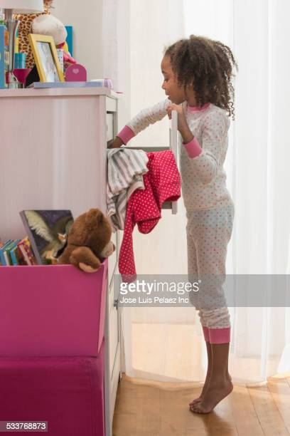 girl picking out clothes in drawers - girl chest stock photos and pictures