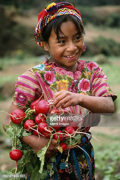 girl (8-10) picking radishes, smiling - guatemala fotografías e imágenes de stock