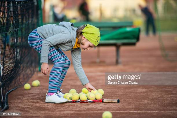 girl picking tennis balls on racket - picking up stock pictures, royalty-free photos & images