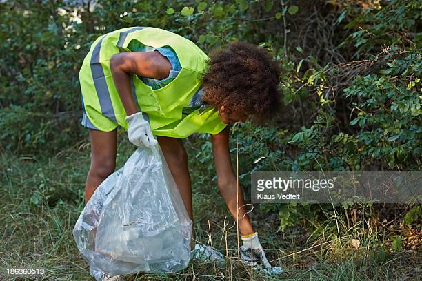Girl picking uå trash in the bushes