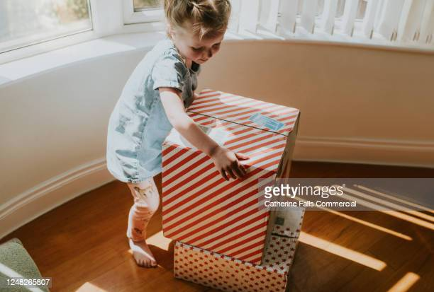 girl picking up a box - sending stock pictures, royalty-free photos & images