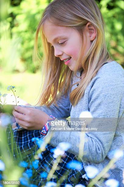 girl picking up a flower in the garden, smiling